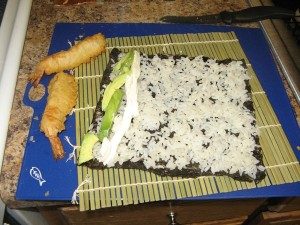 Sushi on its way!  Seaweed paper + avocado slices + cream cheese + sushi rice + tempura shrimp = ...